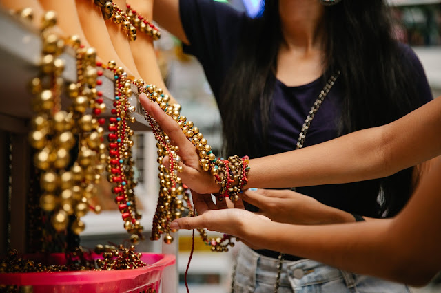 Two persons browsing golden beaded necklaces.