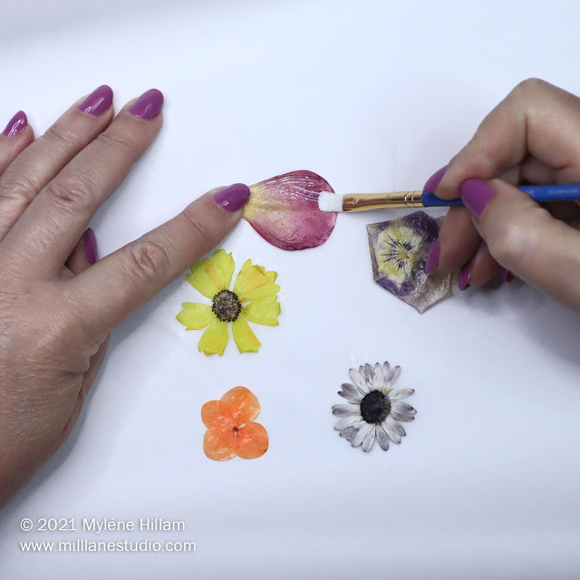 Applying a second coat of Mod Podge to the front of a rose petal with a paint brush