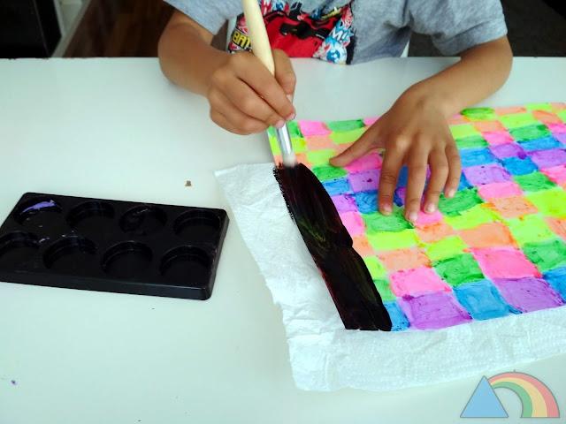 Pintando con pintura negra un papel pintado con colores flúor