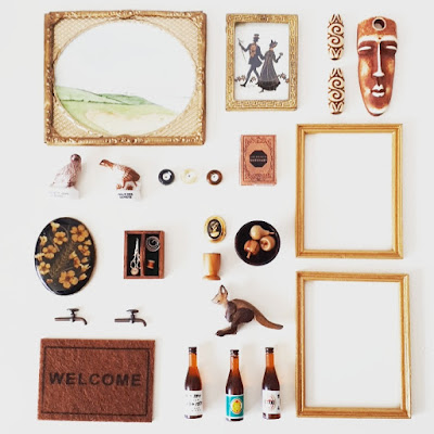 Flat lay of one-twelfth miniature items in black, brown and gold including picture frames, wall art, a sewing kit, wooden fruit and bottles of wine