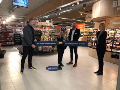 Fyra personer klipper bandet som invigning inne i butiken.
