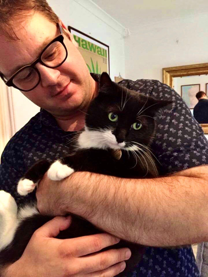 man with glasses holding black-and-white cat