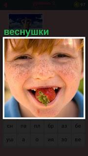 лицо мальчика покрыто веснушками и во рту клубника