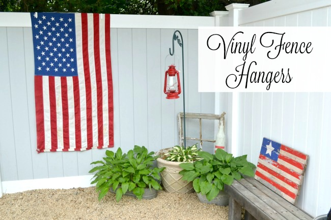 American flag hanging on fence in yard with Pinterest overlay