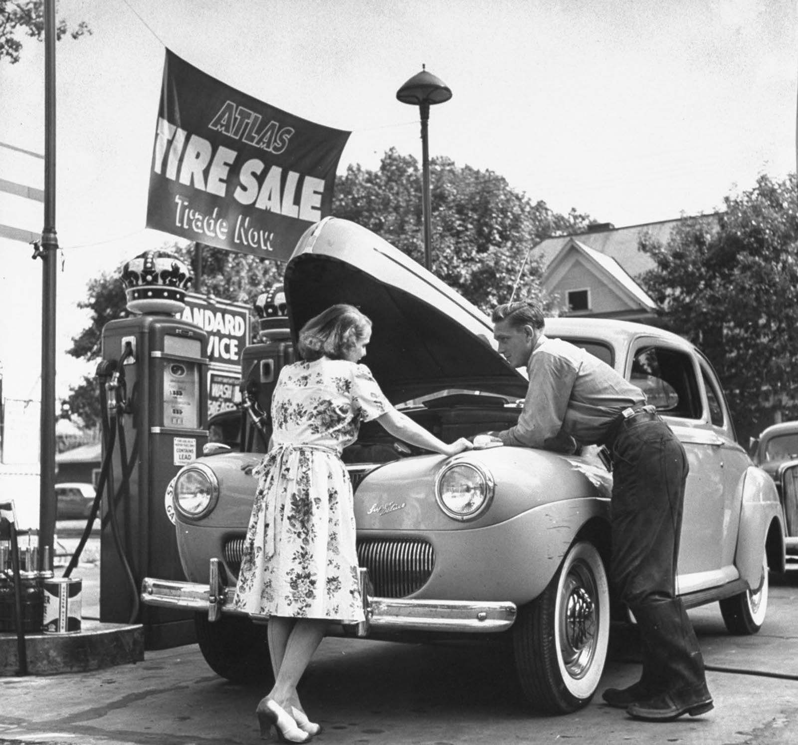Jane conferring with a mechanic at gas station about the car she uses to chauffeur her husband to and from his office, plus get the children back and forth to school.