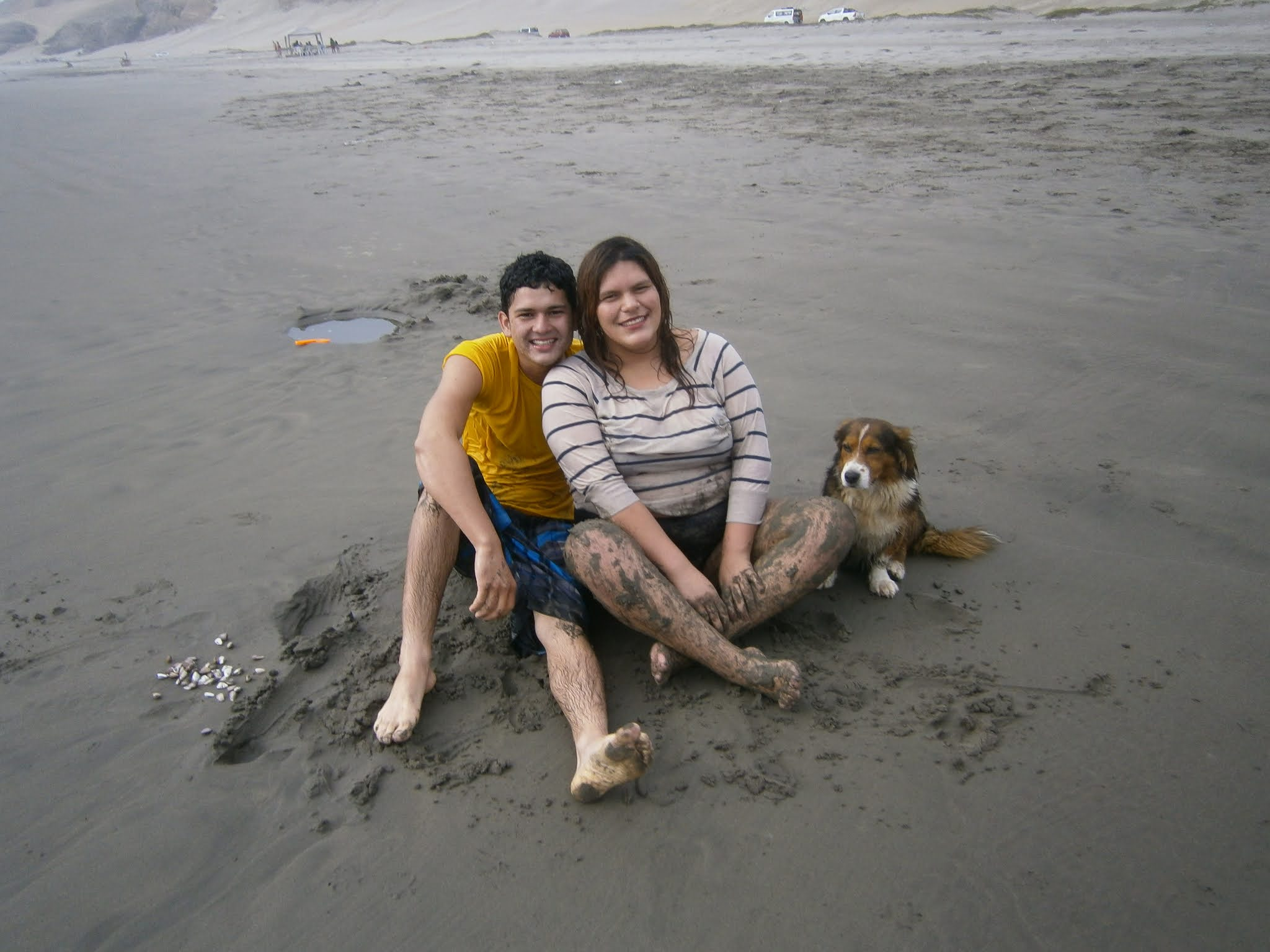 Pareja de enamorados posando para la foto en la orilla del mar y mascota