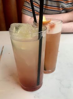 Two glass cylrindical glasses filled with light orange liquid with cylindrical black straws on a bright background