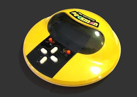[Image: A circularly shaped, brightly colored toy with 6 buttons, a small display and the text 'TOMY ELECTRONIC PUCKMAN'.]
