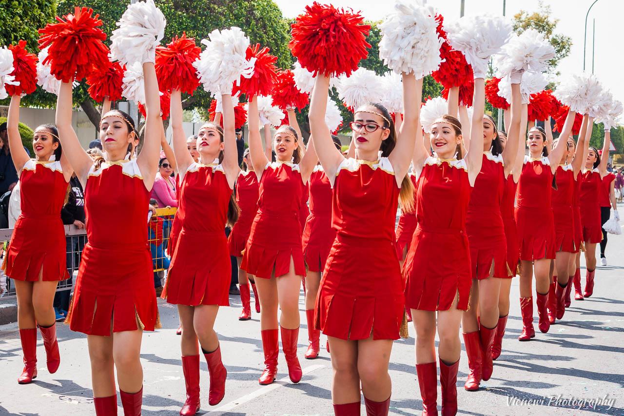 Dziewczęta z pomponami ubrane w czerwone uroczyste stroje przewodzące w paradzie karnawałowej.