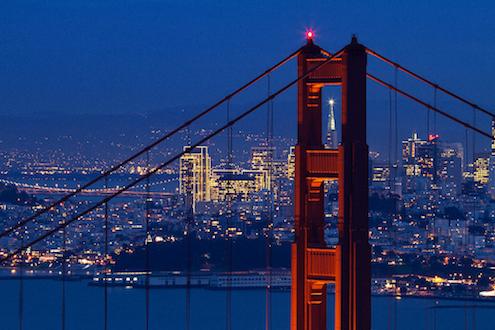 Espectacular detalle de noche de la Pirámide de Transamerica enmarcada en la estructura del Golden Gate Bridge de San Francisco