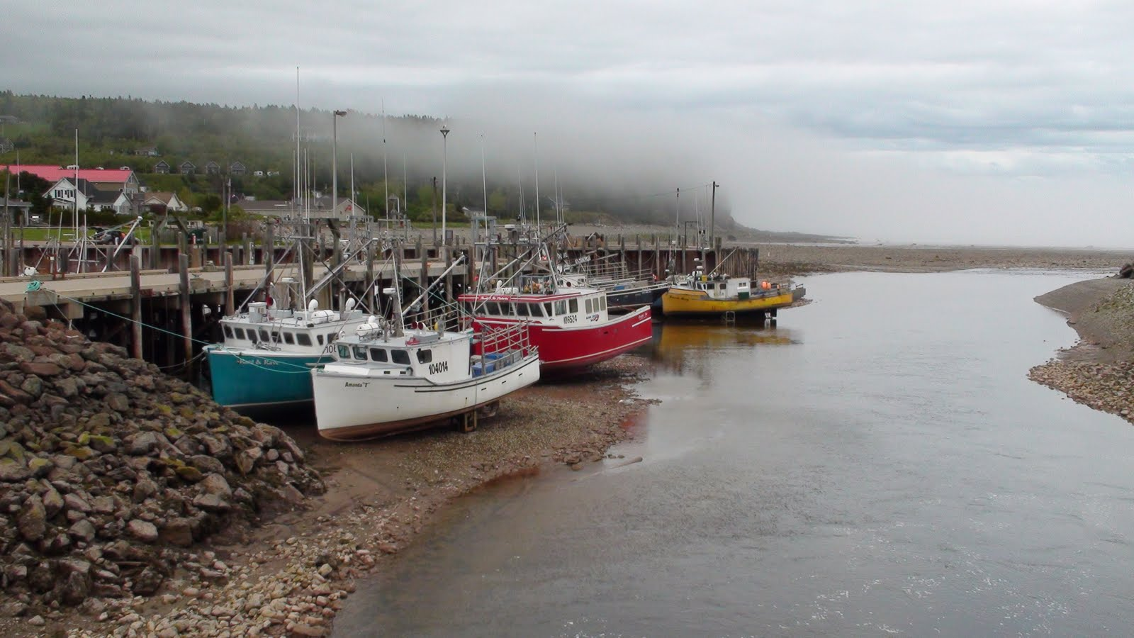 Low tide in the town of Alma on the Bay of Fundy NB. Fishing boats sitting on the bottom of the harbour.