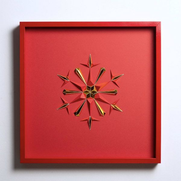 3D red and gold folded paper snowflake in red square frame on wall