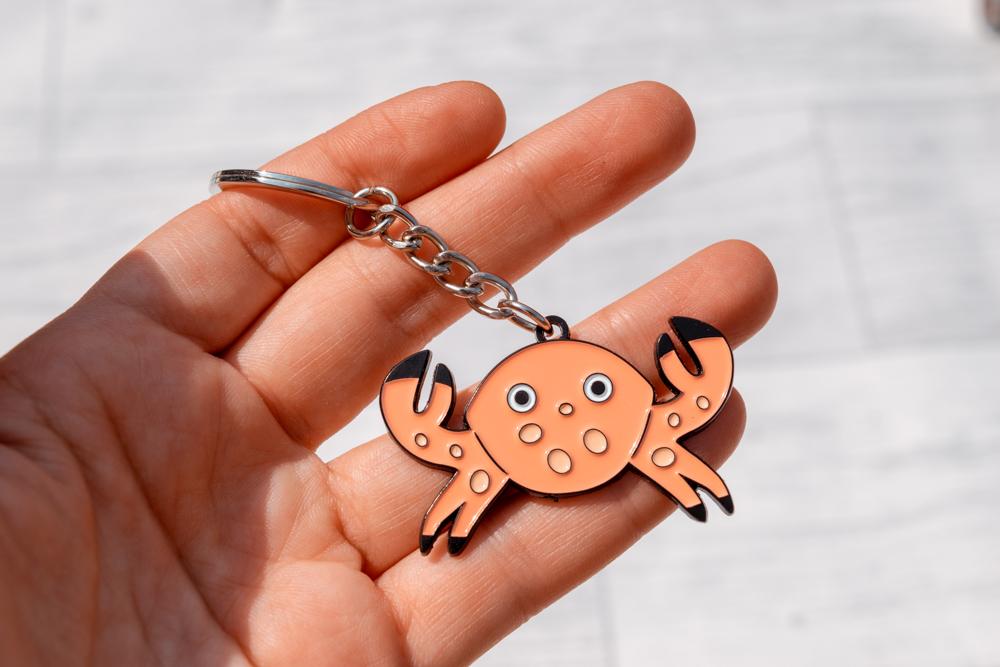 An orange enamel crab keyring