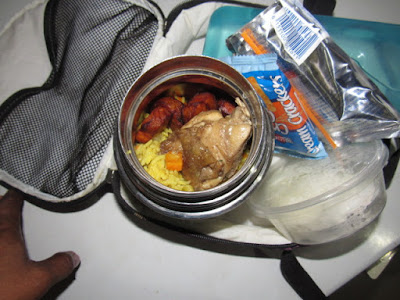 Nigerian school lunchbox meal of fried rice with chicken and plantain