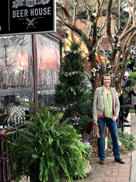 woman in front of Mardi Gras decorated tree