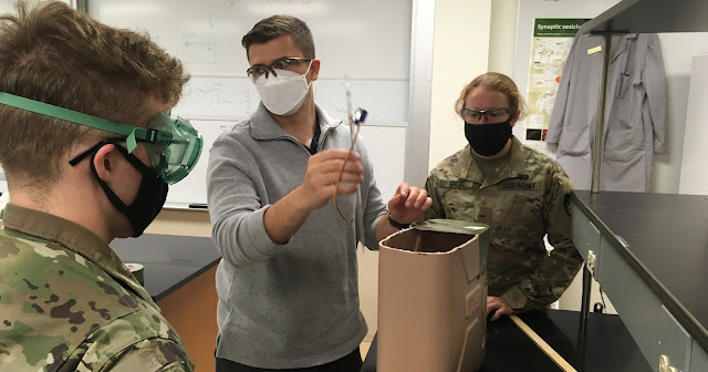 Three people in goggles and masks work with the bubble BPAP.