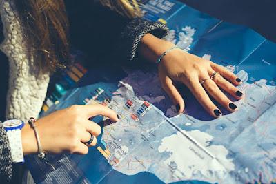 Chica analizando un mapa con su la ruta en coche por Islandia