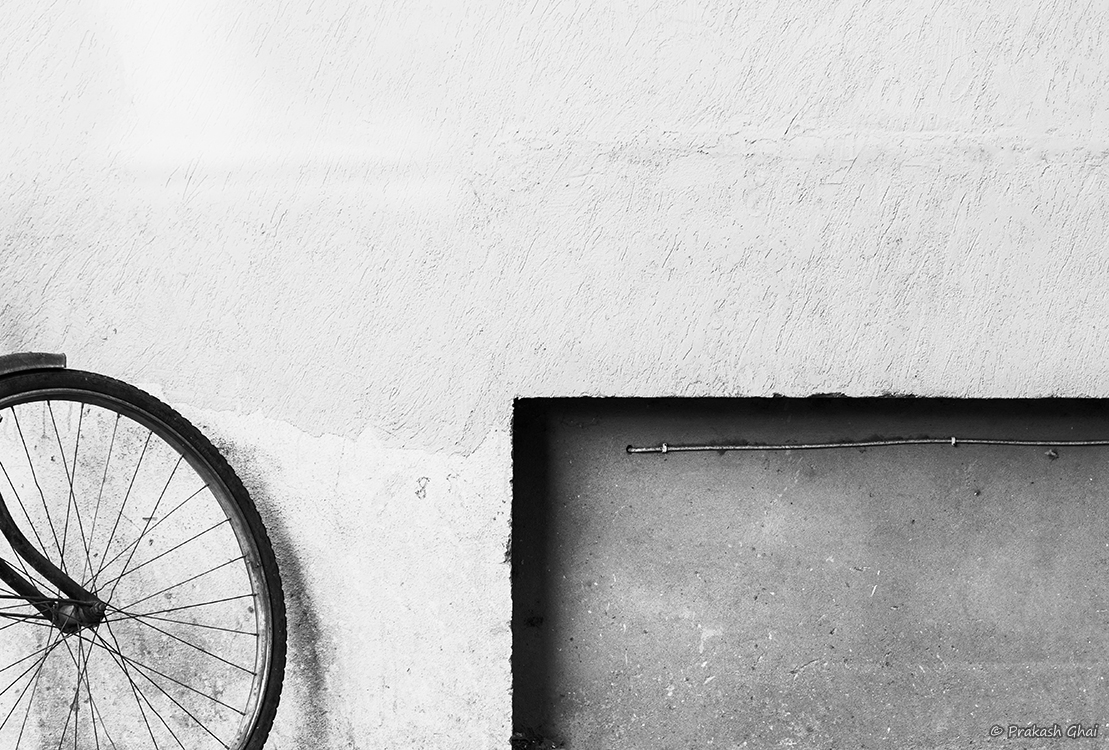 A Black and white Minimalist Photo of the Tyre of a Bicycle parked against a wall and a rectangle on the bottom right.