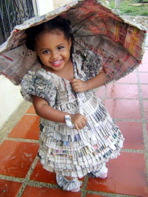 Disfraz hecho con papel de periódico de niña de época con paraguas