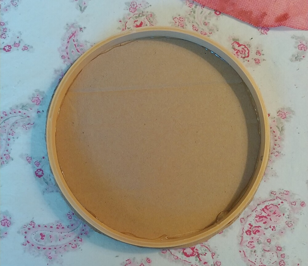 glue the embroidery hoop to the cardboard bacing