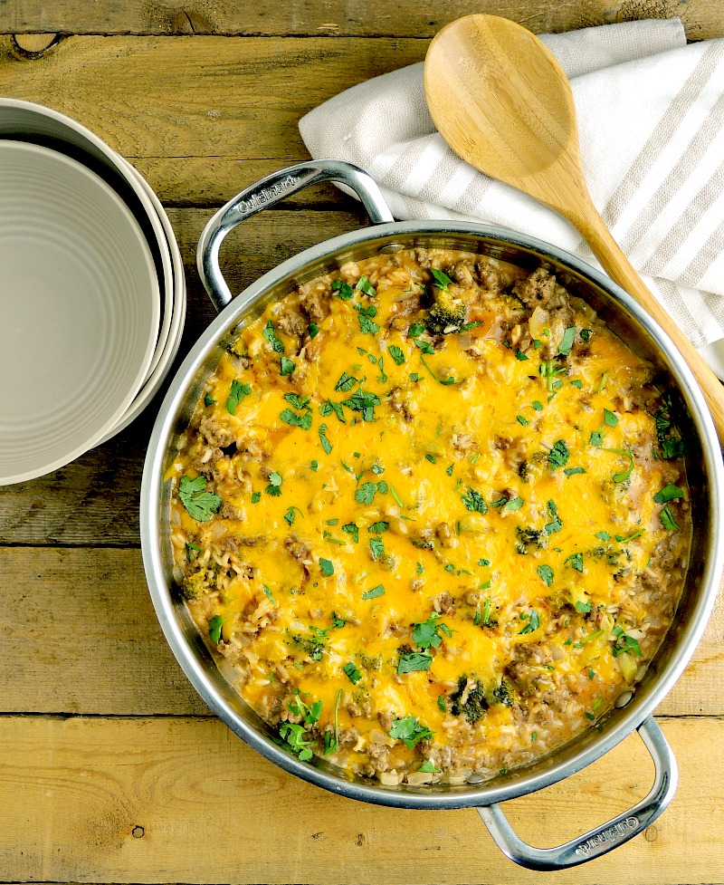 Cheesy Beef and Broccoli Rice Skillet with a wooden spoon in a silver skillet on a wooden table.