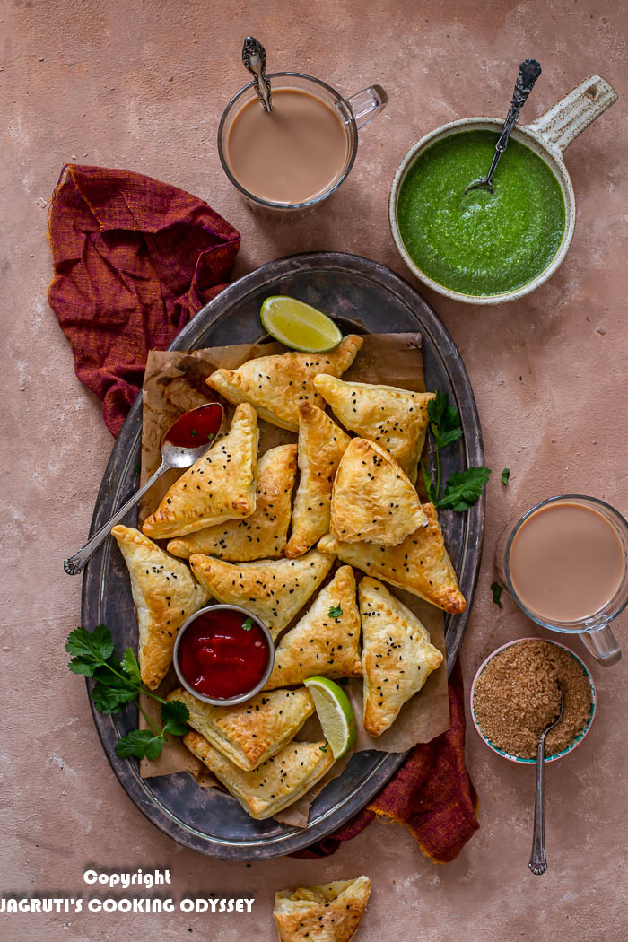 Air fryer punjabi samosa puffs in a oval tray, served with ketchup and chai tea.
