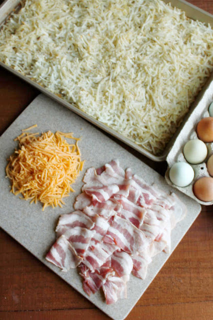 partially cooked hash browns in sheet pan getting ready for eggs, cheese and pieces of bacon