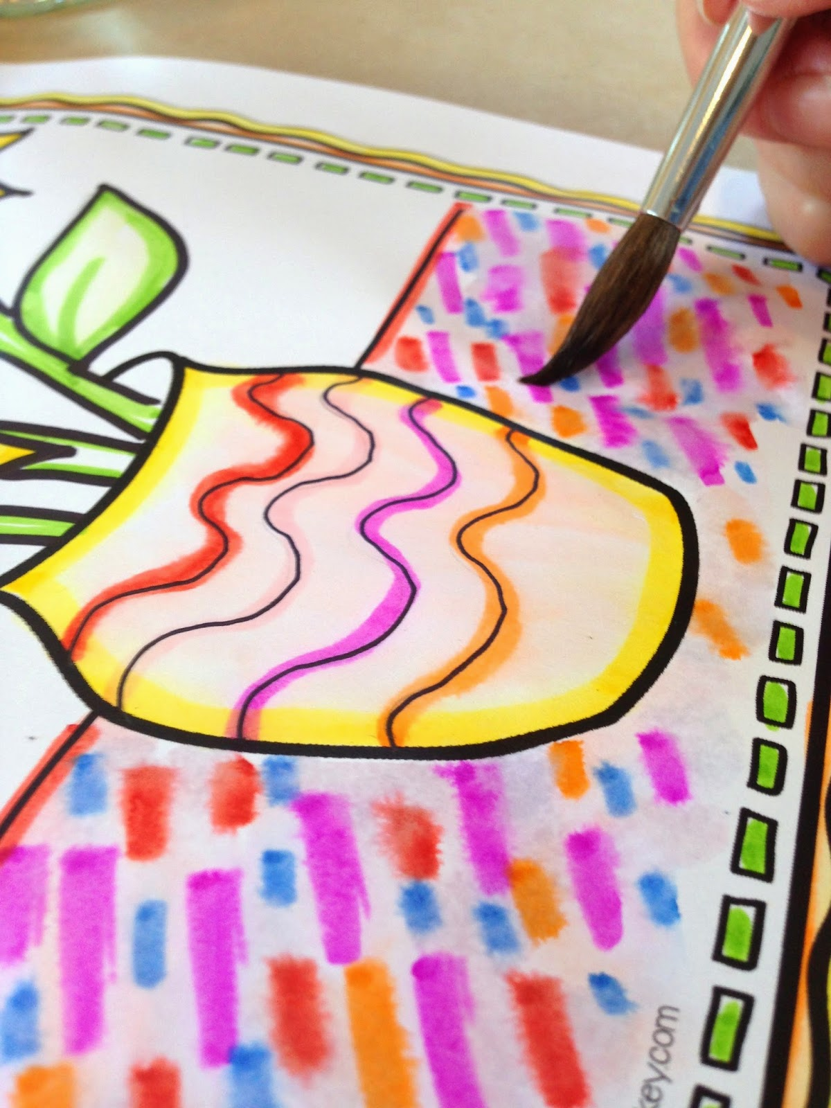 Expressive Monkey demonstrates how to use markers and water on a sunflower drawing.