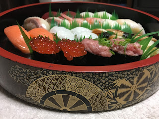 A picture of various kinds of home-delivered sushi in a decorative pseudo-laquerware box called a sushi-oke