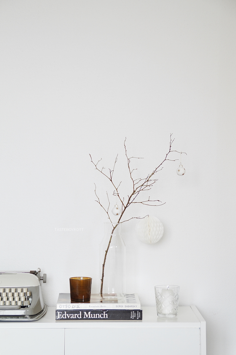Zweig mit Mini-Christbaumkugeln und Wabenball und Kerzen als schlichte Weihnachtsdeko