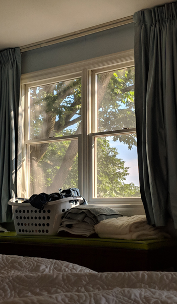 image of my bedroom window, through which can be seen a leafy green tree; my window is surrounded by blue drapes, and beneath it is a window bench, atop which sits a laundry basket and clean folded laundry