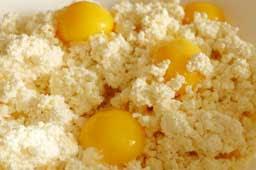 добавляем ванильный сахар , манку и 50 г мягкого сливочного масла , перемешиваем