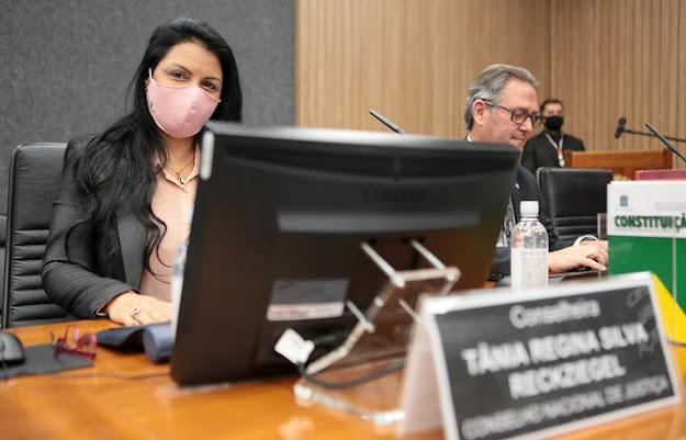 A imagem mostra a conselheira do CNJ Tânia Regina, sentada em uma mesa com um computador a sua frente.