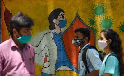 Warga berjalan melewati mural dinding yang menggambarkan seorang petugas kesehatan mengenakan masker sambil memegang vaksin dan perisai untuk menyebarkan kesadaran tentang virus corona Covid-19, di Mumbai pada 30 Juni 2021. AFP