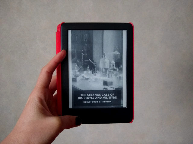 A hand holding a black kindle with a red cover with the book.