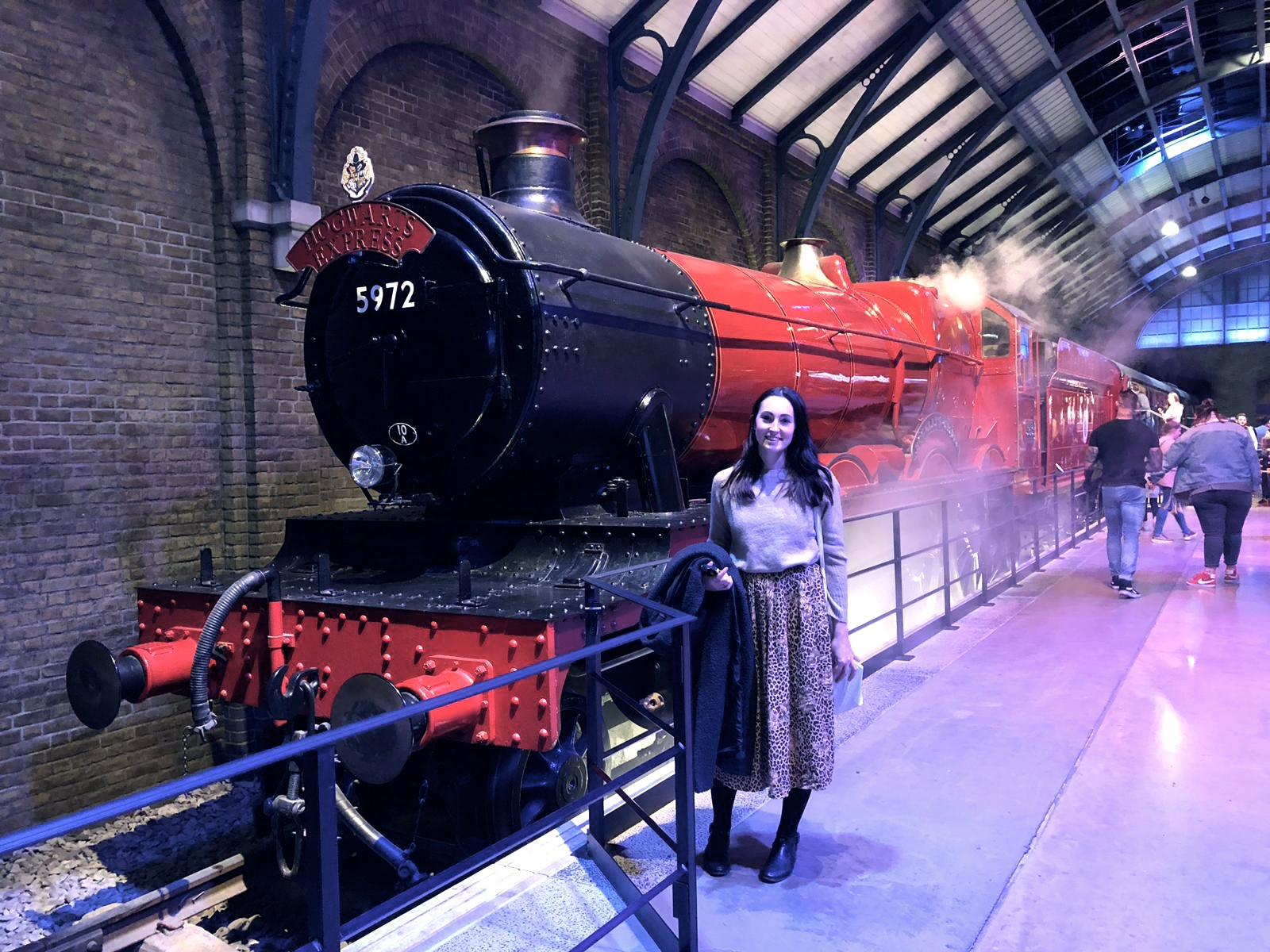 Standing in front of the Hogwarts Express, wearing a midi skirt and jumper