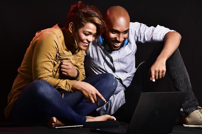 Foto de um homem e uma mulher sentados no chão assistindo vídeo no notebook
