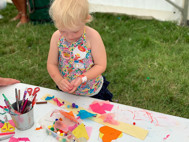 A toddler making a paper crown with tissue paper, balls and stickers at a children's festival