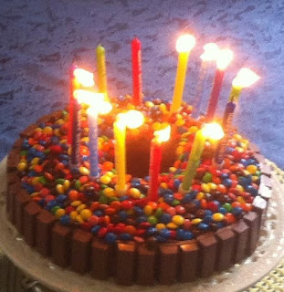 Home-cooked birthday cake: chocolate sponge ring cake with kit-kat sides to contain the candy buttons covering the top. Most of the birthday candles standing in a ring are topped with flame but a few have been blown out already. May wishes come true!