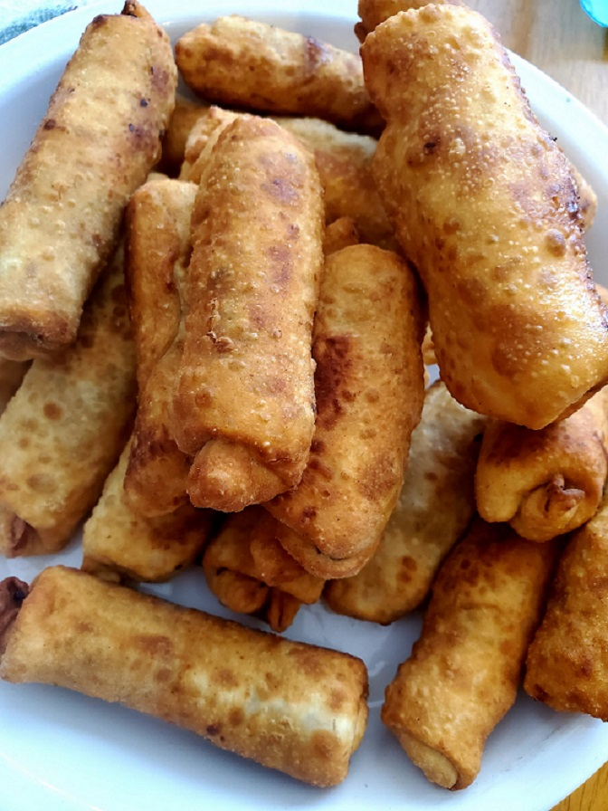 pork filled fried homemade egg rolls in a white dish cooling