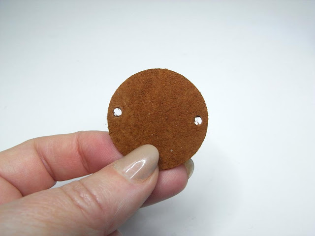 Brown suede circle with holes punched on opposite sides
