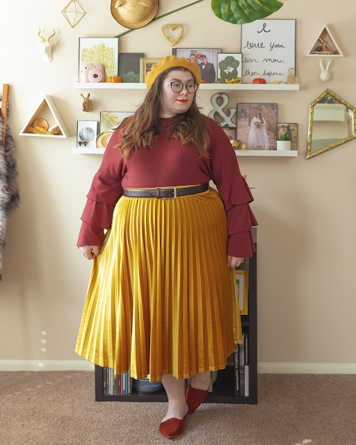 An outfit consisting of a mustard yellow beret, a rust brown red tri tiered long sleeve blouse tucked into a mustard yellow velvet pleated midi skirt and rust red pointed toe mules.