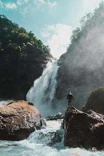 person standing by waterfall and the river flowing from it in daylight