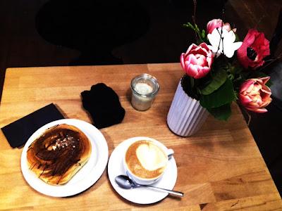 Draufsicht auf Holztisch mit Kaffee und Zimtschnecke