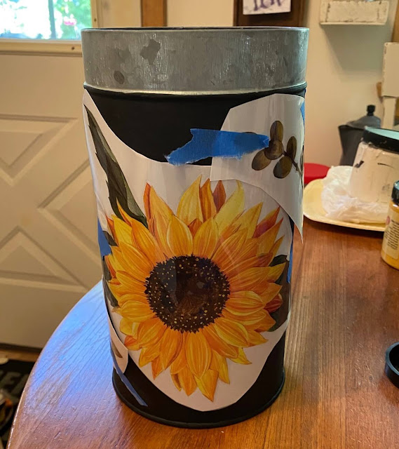 Photo of sunflower decor transfers being arranged on a canister.