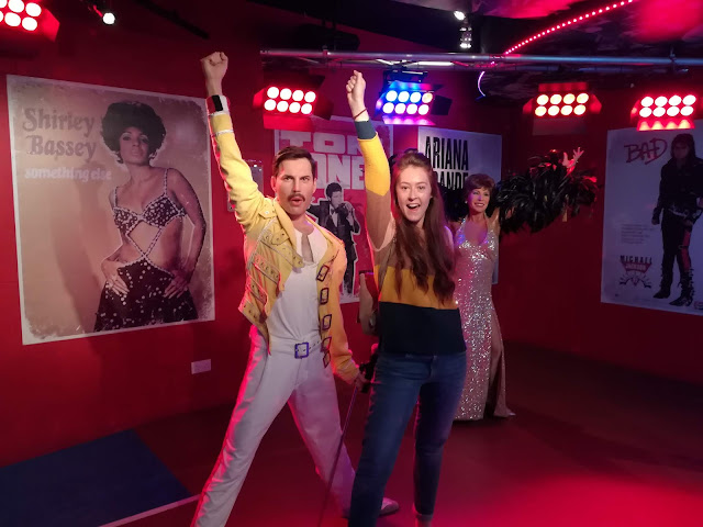 Me stood next to a waxwork of Freddie Mercury wearing his white trousers and yellow jacket