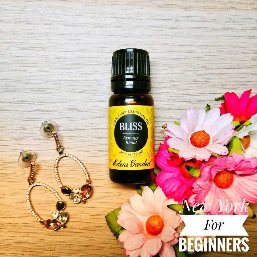 Picture of Edens garden bliss essential oil blend with flowers and earrings