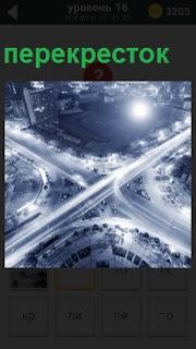 Ярко освещенный перекресток в многолюдном городе, по которому осуществляется движение автомобилей