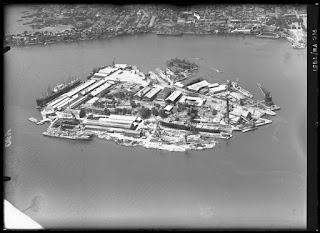 Greyscale aerial photograph of a heavily industrialised island in the middle of a grey sea, a city visible on land in the distance.