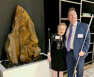 Diane McGeorge and National Federation of the Blind President Mark Riccobono at the Jernigan Institute stand in front of a replica McGeorge fountain. The broad base is white, about table-height, filled with round, black stones where water falls and splashes. Rising up from the rocks more than a foot above the head, is the rough-surfaced sharp mountain peak in reds, rusts and browns